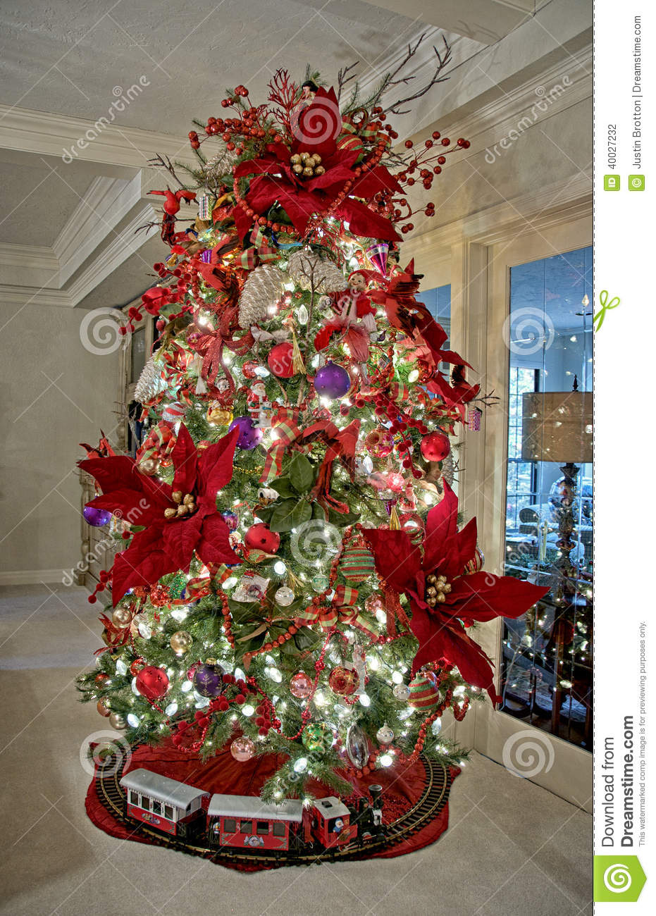 this is a christmas tree decorated with ornaments with poinsettia flowers
