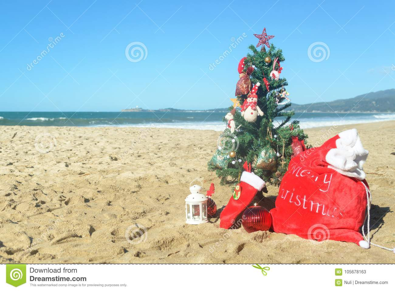 christmas at the beach red santa bag of presents stockings and decorated tree in the sand on sunny day - Christmas At The Beach