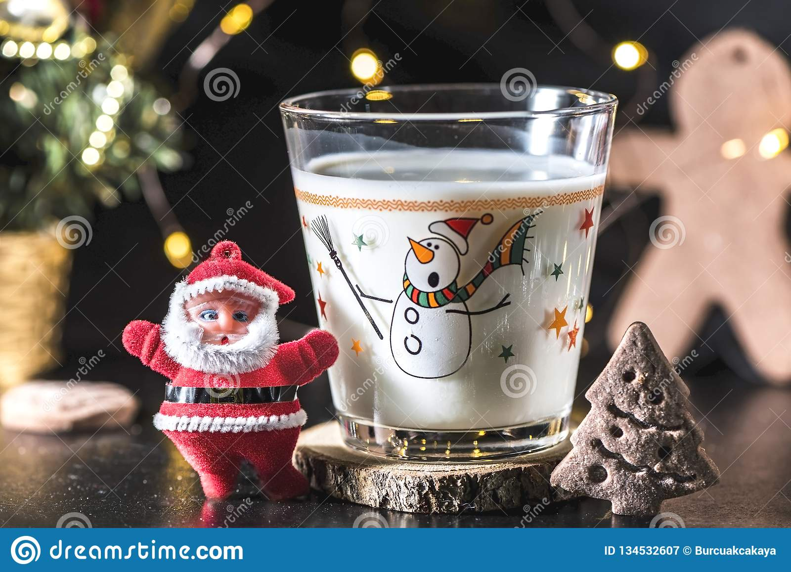Christmas tree shaped cookie and a glass of milk for Santa Claus, close up, indoor. Holiday concept