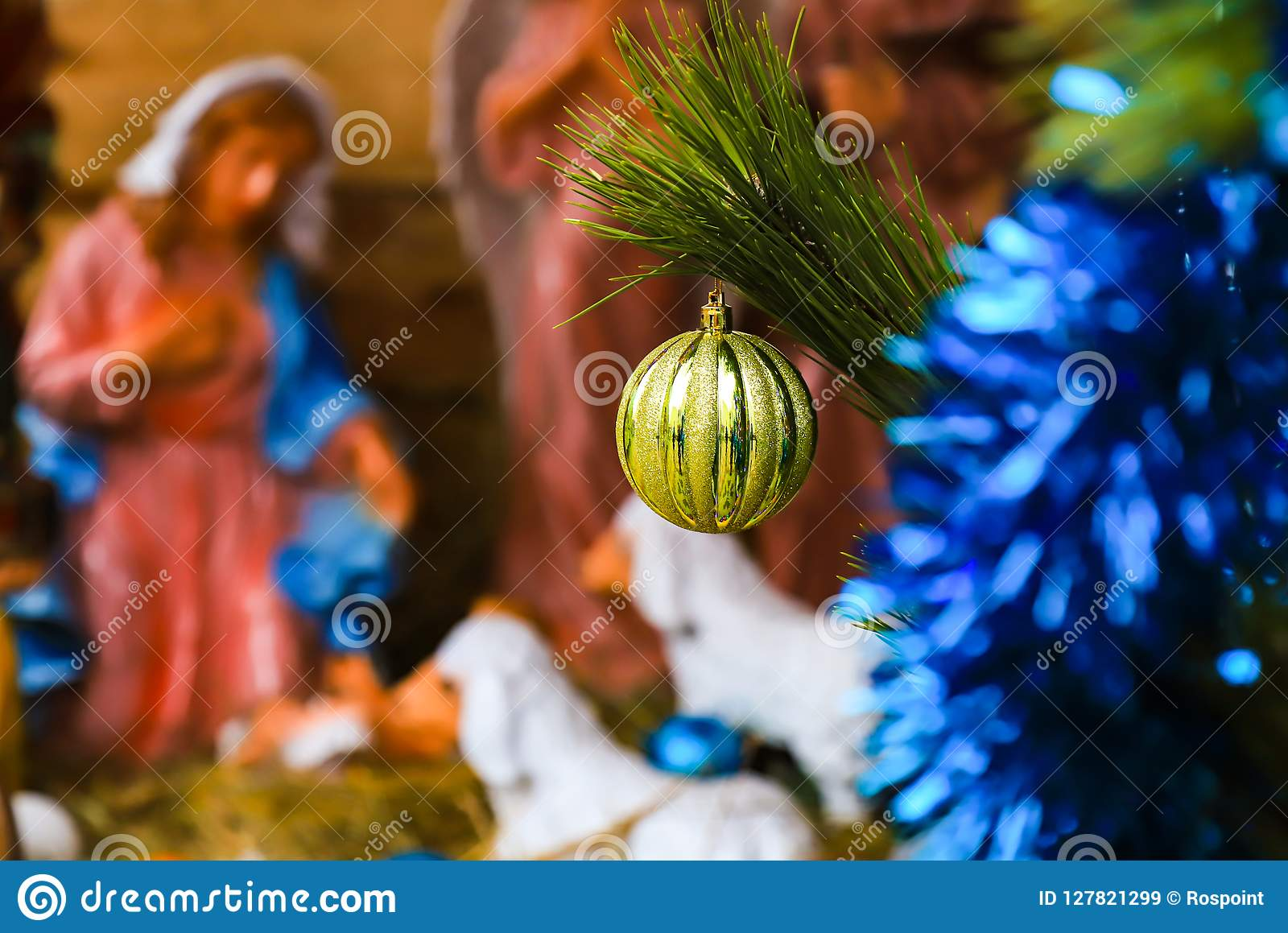 Christmas tree toy, yellow ball, on the background of a blurred image of the Christmas scene of the birth of Christ