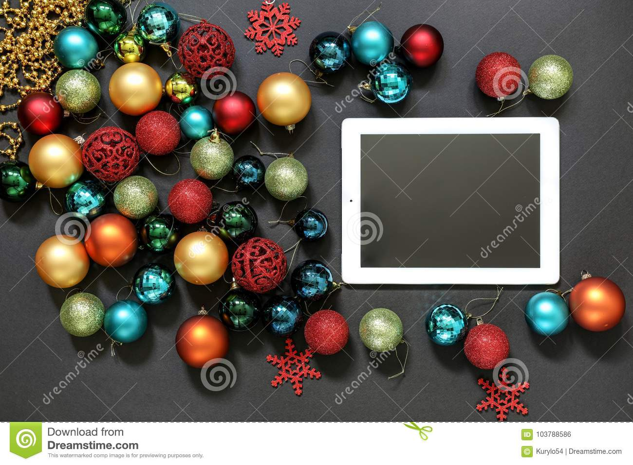 christmas tree toys balls and ipad on dark background