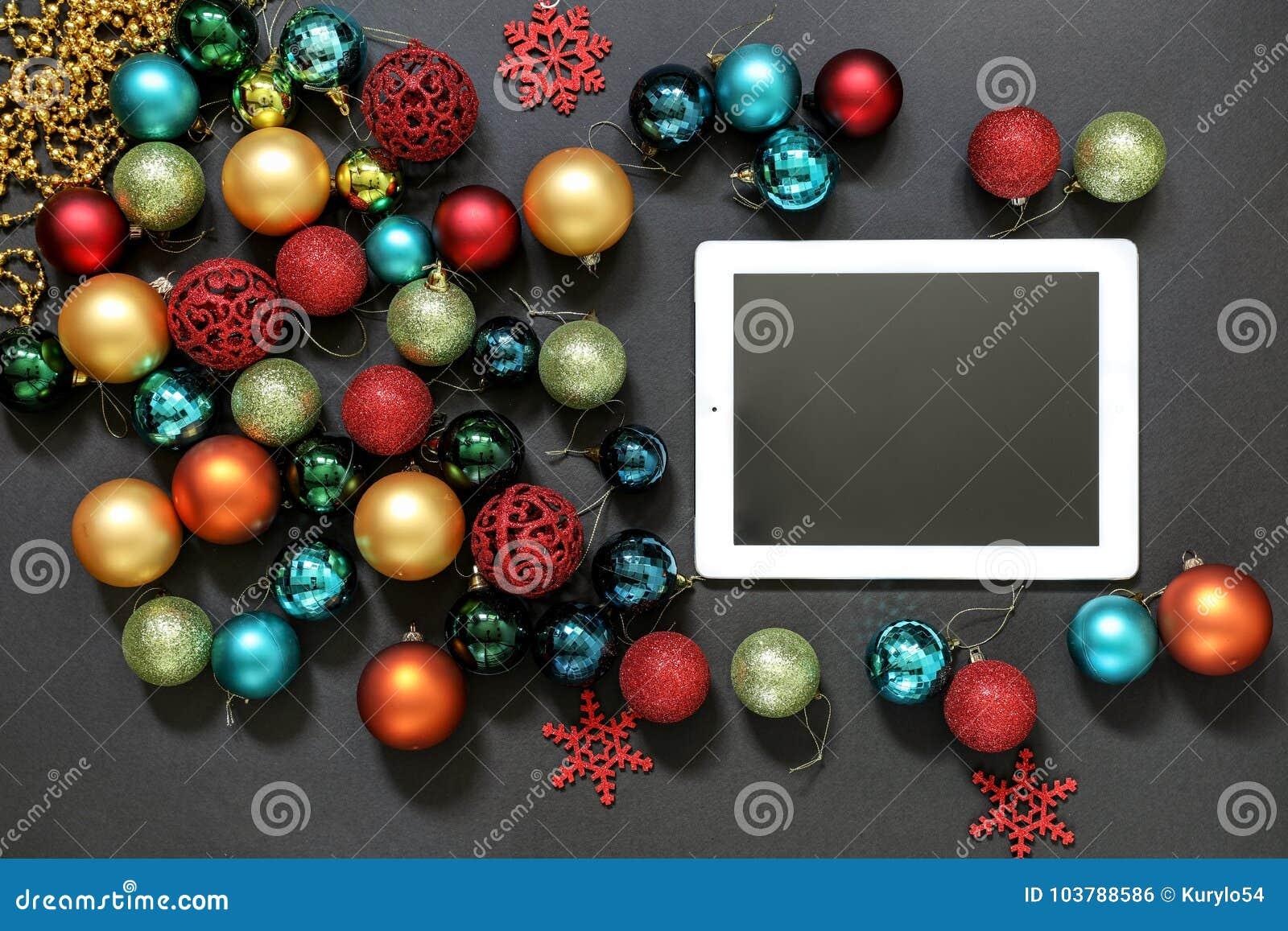 christmas tree toys balls and ipad on dark background
