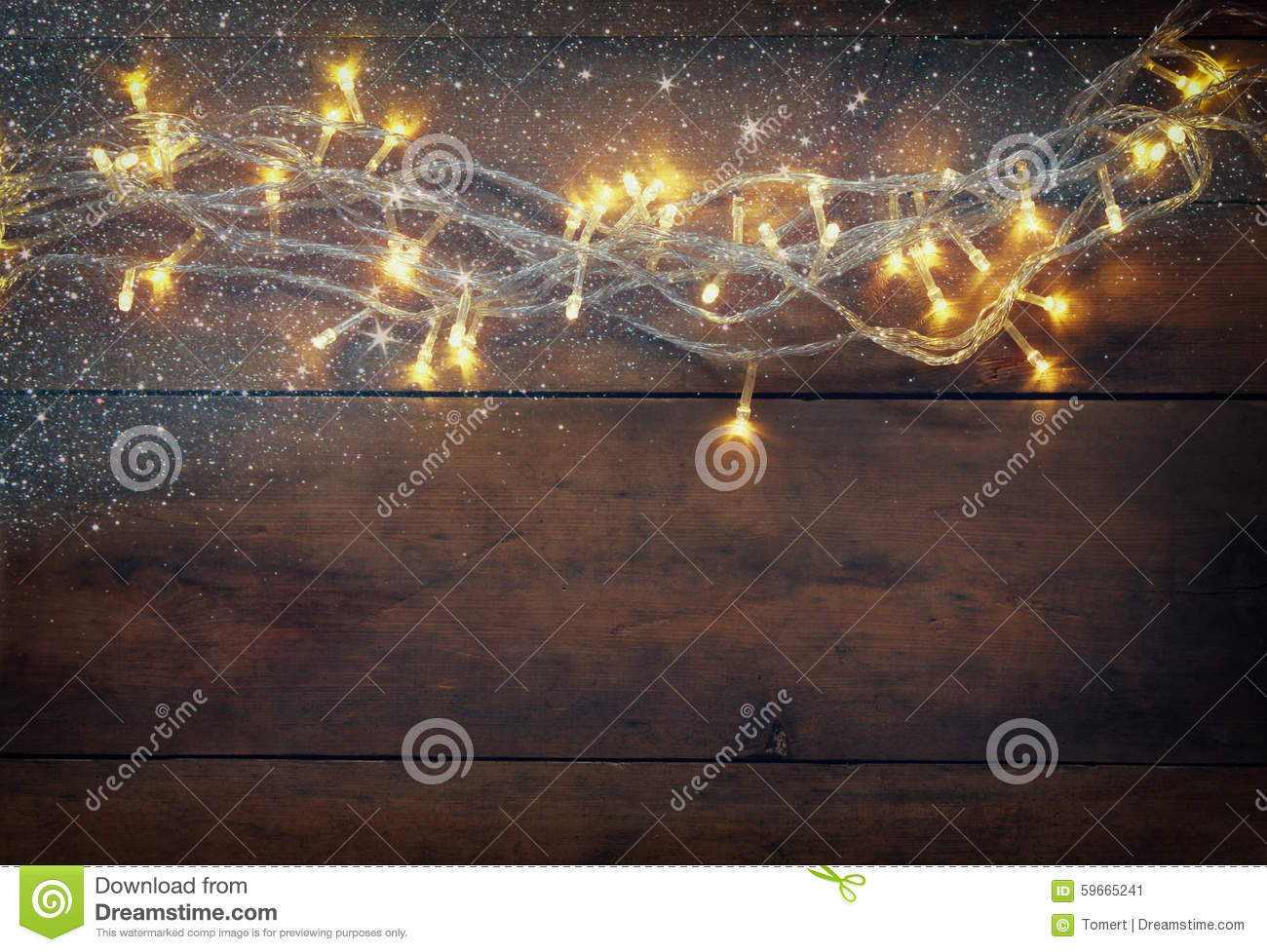 Christmas warm gold garland lights on wooden rustic background. filtered image with glitter overlay
