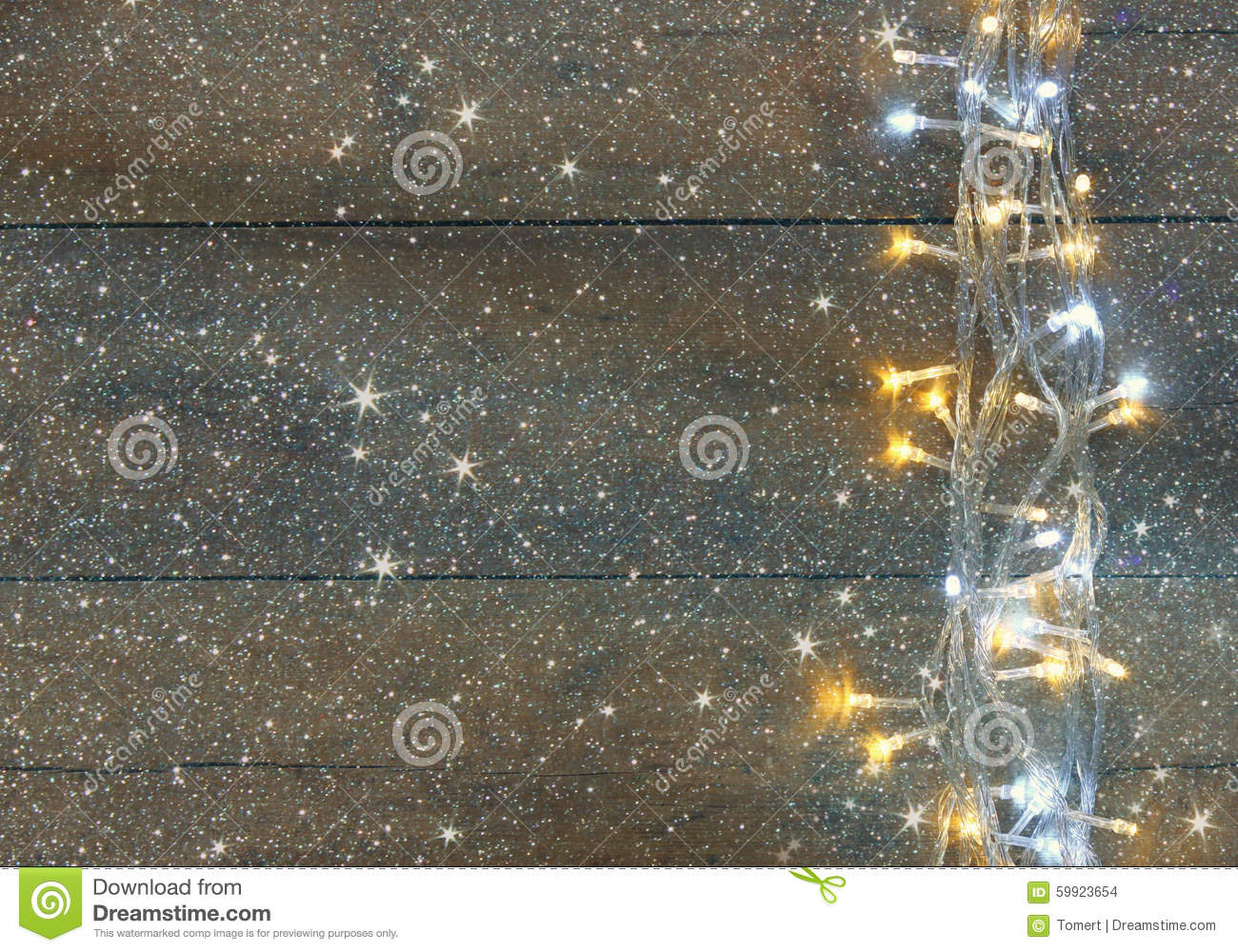 Christmas warm gold garland lights on wooden rustic background. filtered image with glitter overlay.