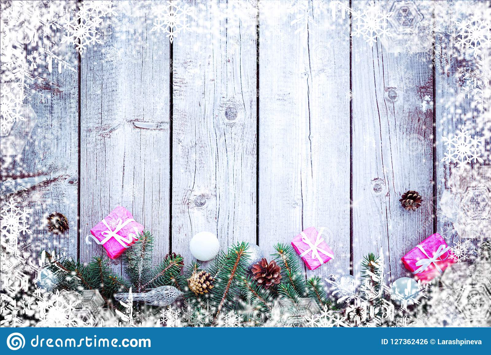 Christmas winter holiday background with gifts boxes with fir branches, pine cones, New Year balls on wooden table.