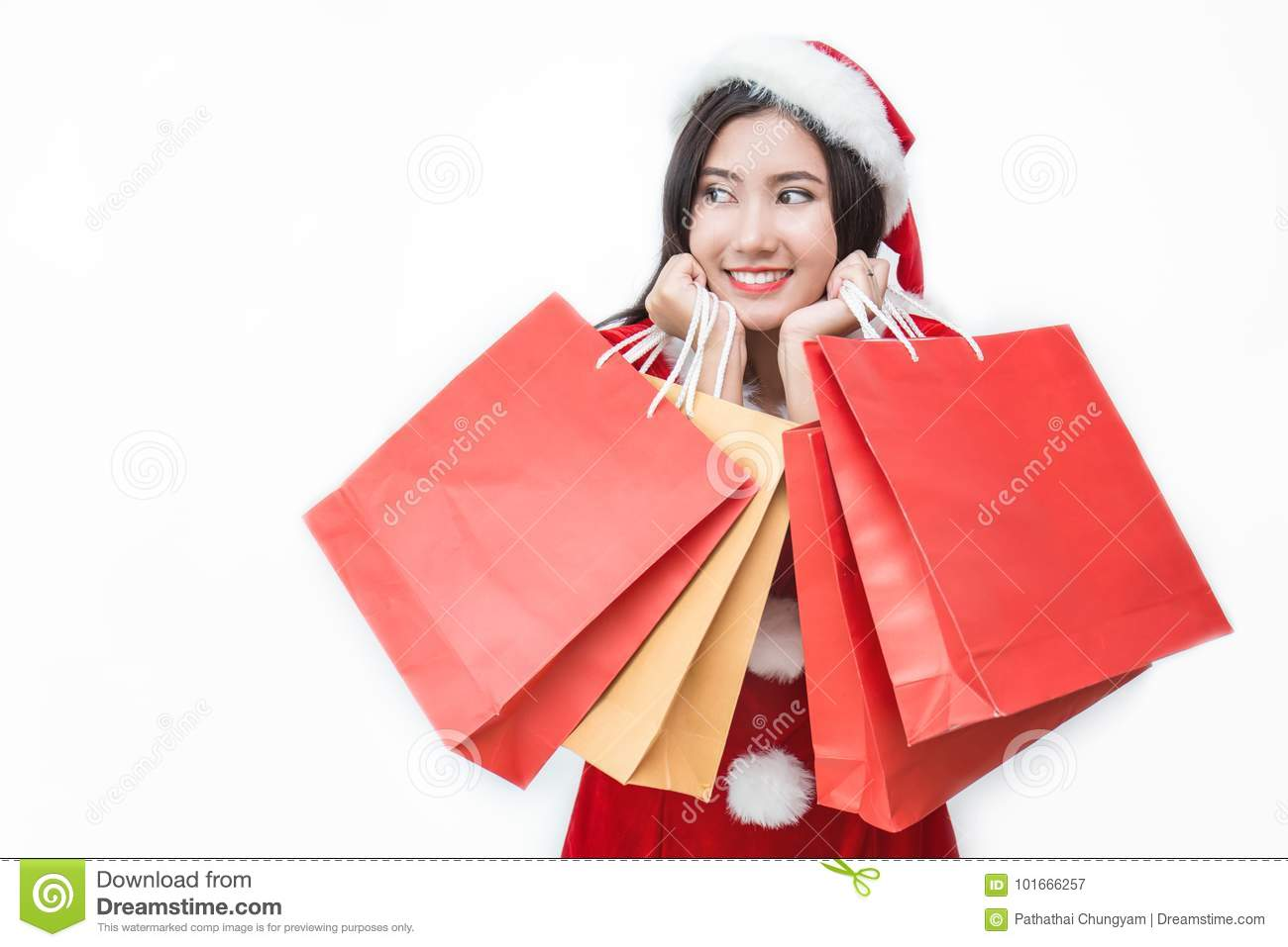 a9edb1997c609 Christmas winter shopping. Asian woman in santa claus hat standing holding  shopping bags excited isolated on white background.