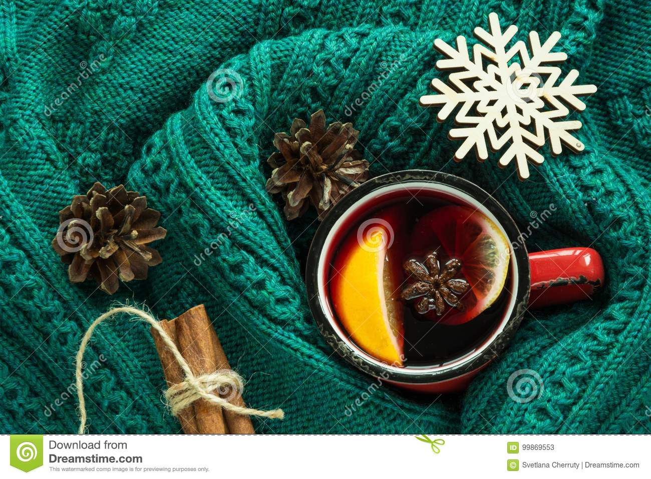 Christmas and winter traditional hot beverage. Mulled wine in red mug with spice wrapped in warm green sweater.