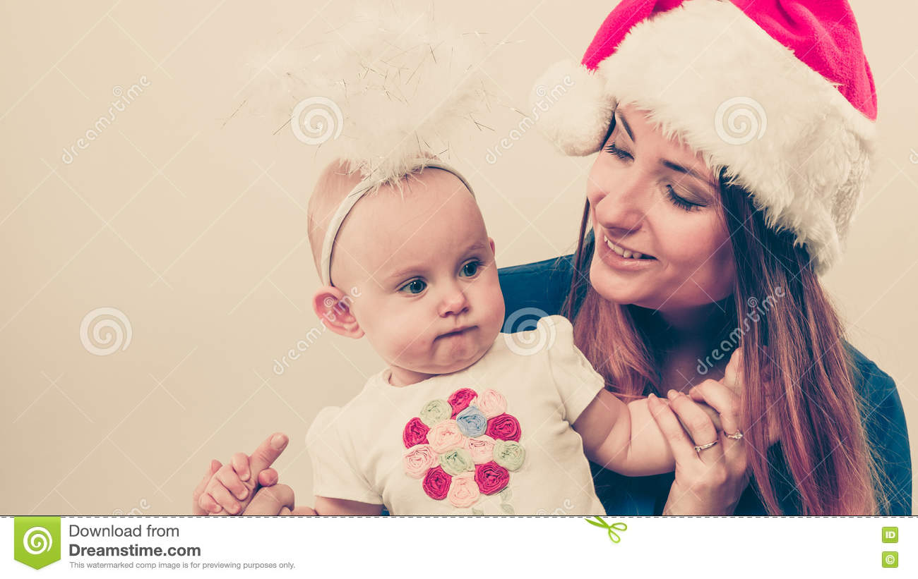 543625e55232d Family celebration concept. Christmas women with cute baby. Beautiful lady  has red santa claus cap.