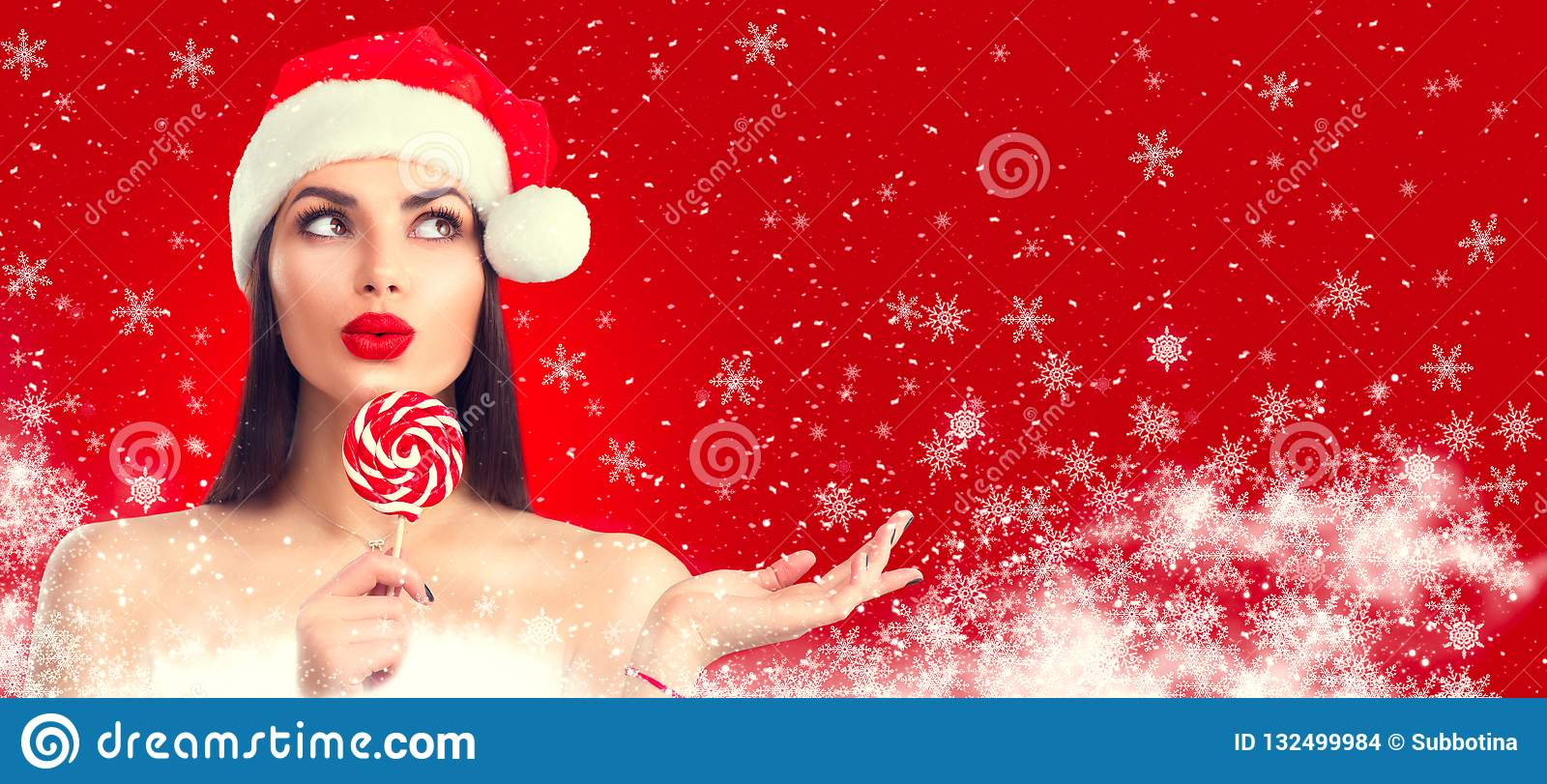 Christmas woman. Joyful model girl in Santa`s hat with lollipop candy pointing hand, proposing product. Surprised expression