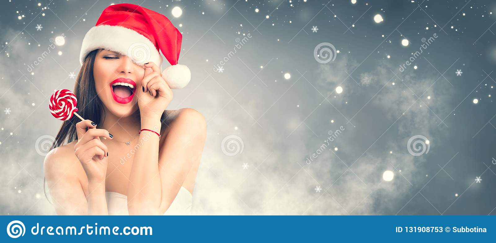 Christmas woman. Joyful model girl in Santa`s hat with red lips and lollipop candy in her hand