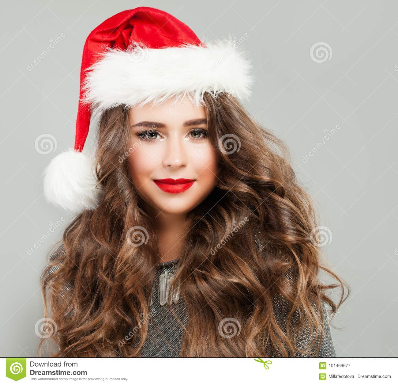 e64c912f1e1ba Christmas Woman wearing Santa Hat. Cute Young Woman Fashion Model with  Curly Hair and New Years Party Makeup