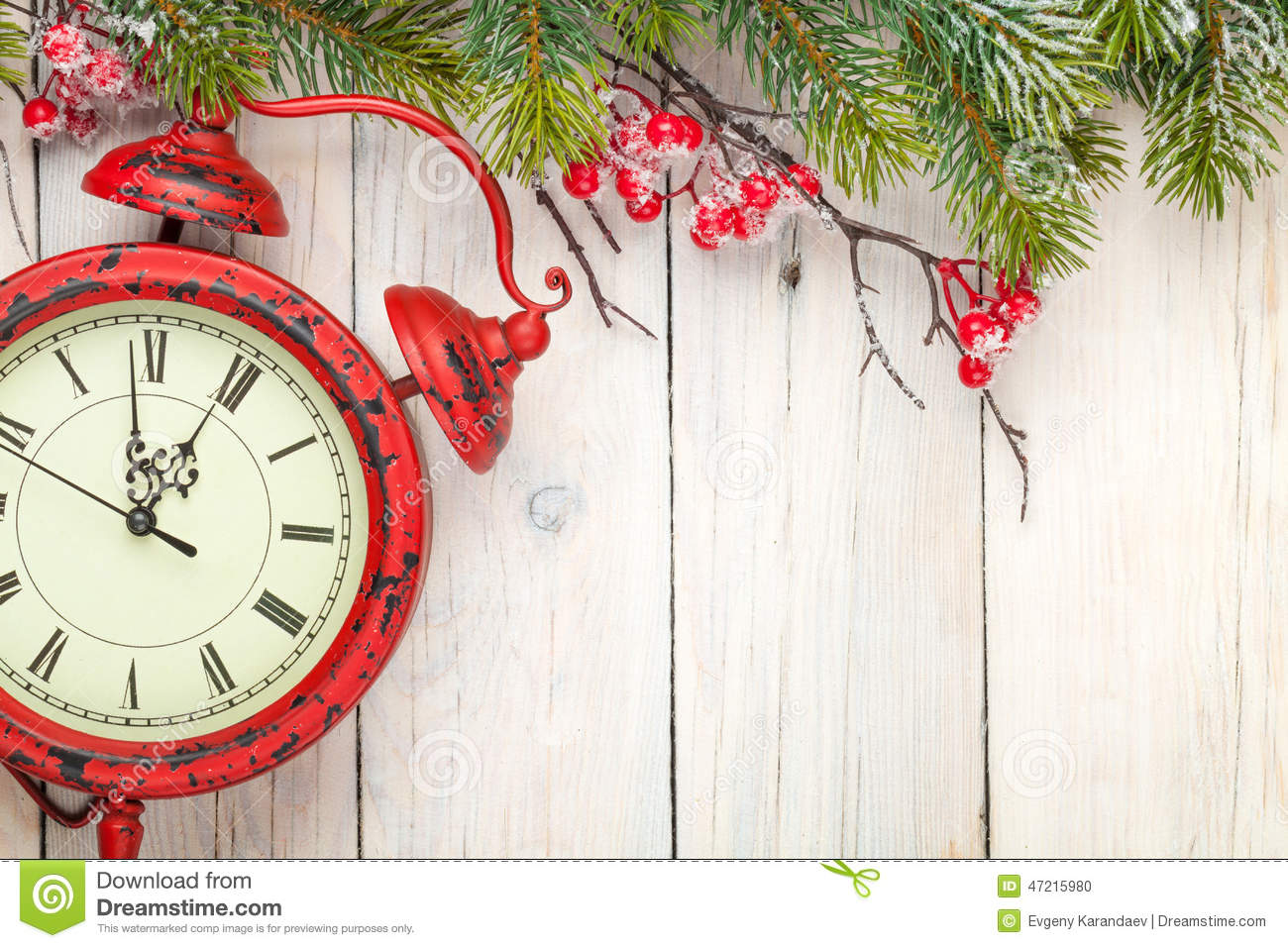 Christmas wooden background with fir tree and antique alarm clock