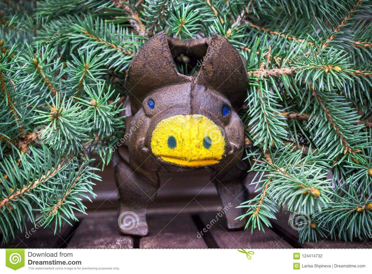 Christmas composition with brown / earthen pig, yellow nose and fir branches on a wooden table, New Year concept, 2019 year - yell
