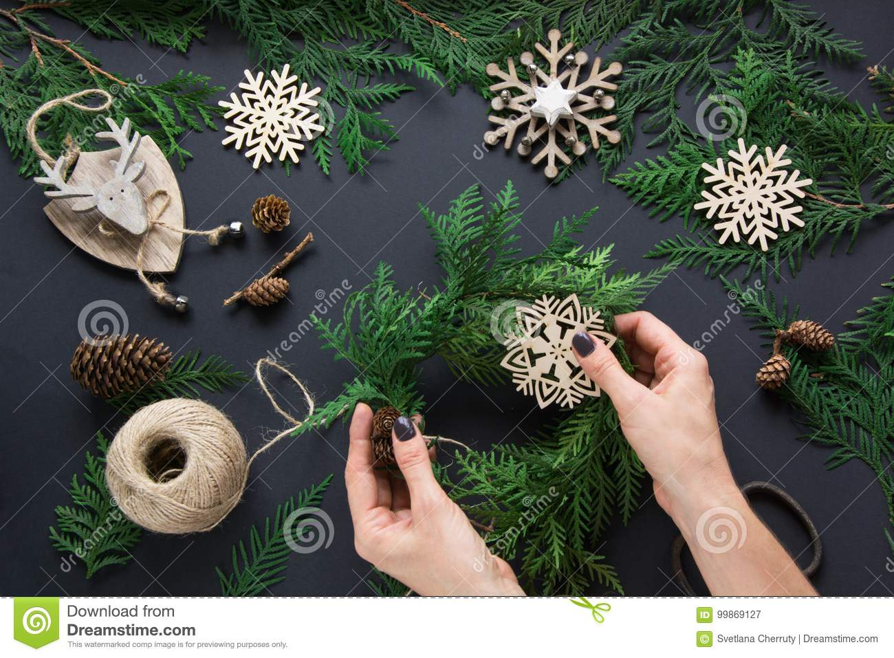 Christmas workshop of wreath, decor, twine, twigs and snowflakes. Woman prepare a wreath. Top v