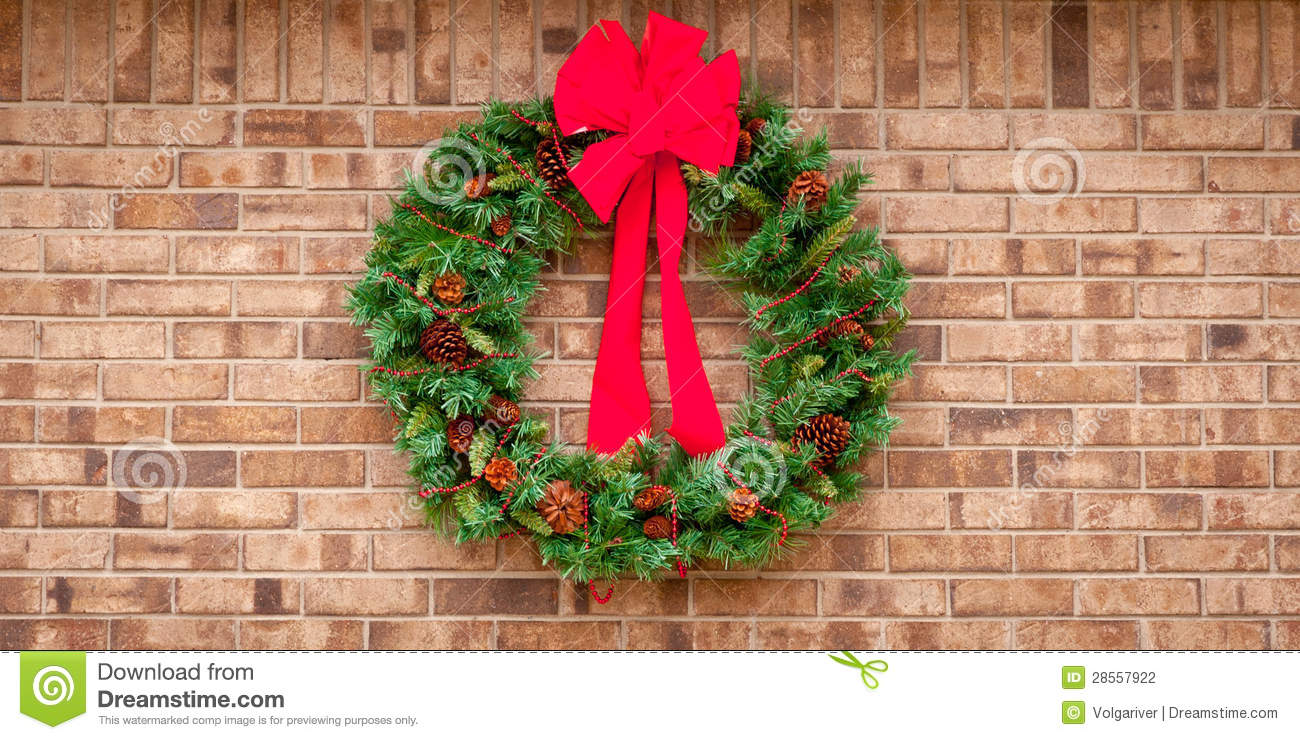 Christmas Wreath Hanging On A Brick Wall With Co Stock