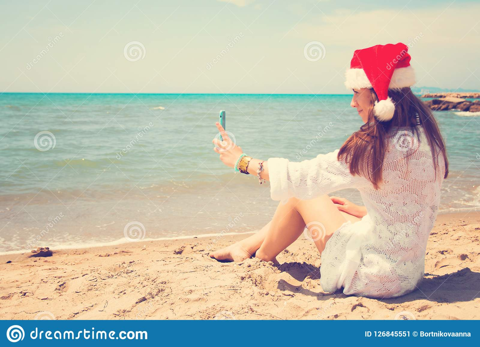 Christmas young smiling woman in red santa hat taking picture self portrait on smartphone at beach over sea background. toned