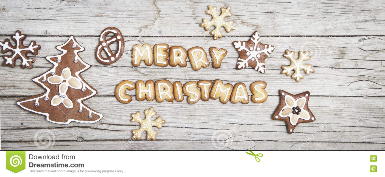 Christmassy grey wood background with gingerbread and Merry Christma`s letter