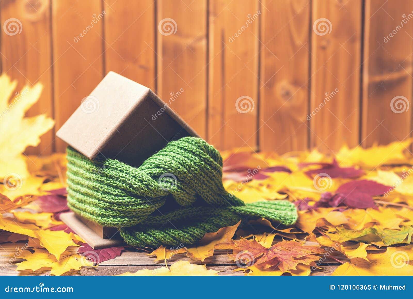 Chronienia i wyodrębniania dom Szalik wokoło domu modela na drewnianym stole Mała miniatura dom w ciepłym szaliku na jesień liści