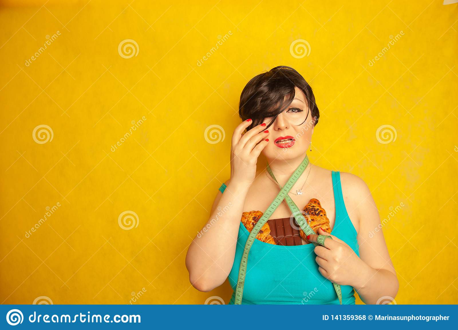 Chubby girl unhappy with fashion standarts and sad with a centimeter tape and high-calorie food, she is crying
