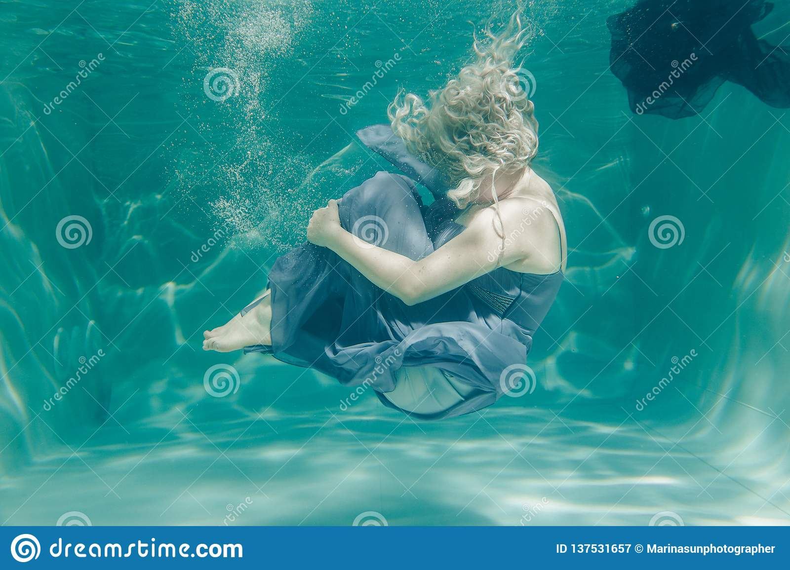 Chubby woman in grey evening long dress swimming underwater on her holidays and enjoy with relax