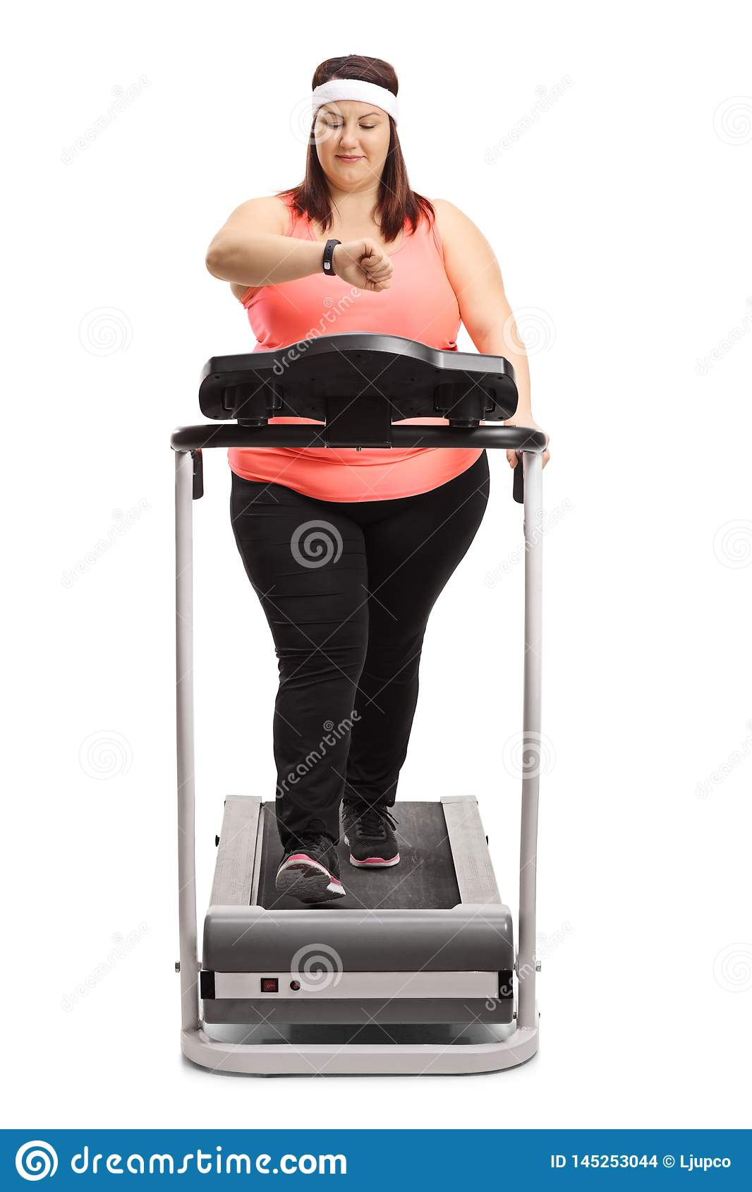 Chubby woman on a treadmill checking her fitness band