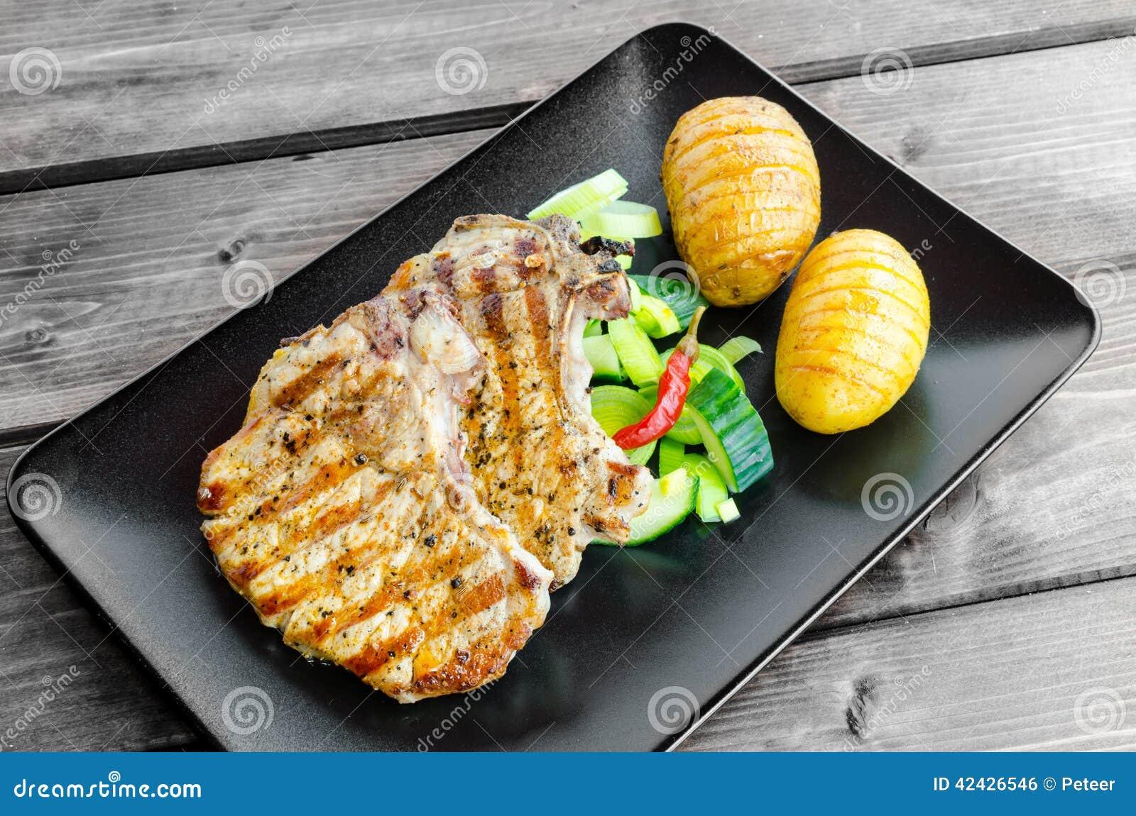 Chuleta asada a la parrilla con las verduras y las patatas asadas