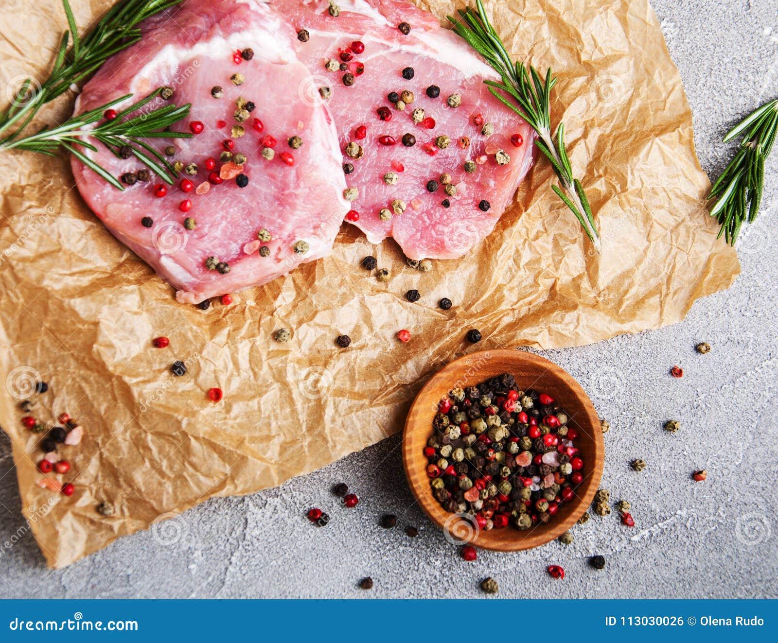 Chuletas de cerdo crudas frescas con las especias y las hierbas