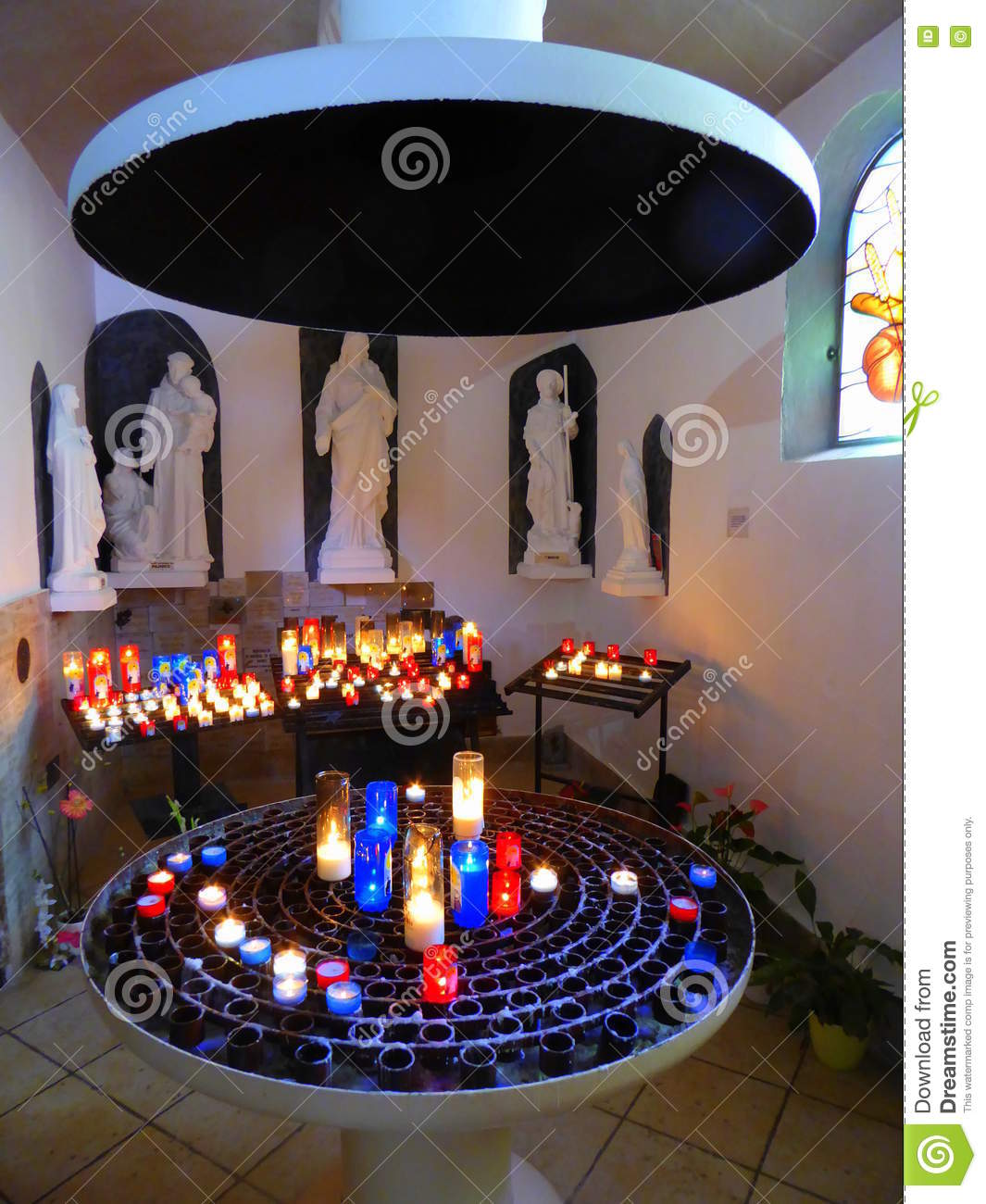 Lighted candles and statues in chapel