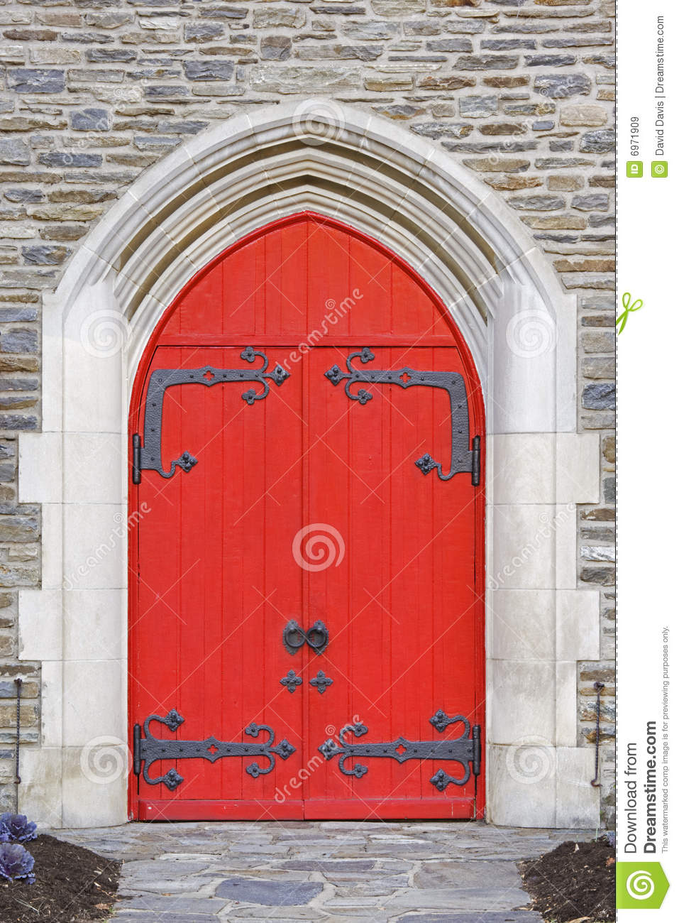 Red church doors on a old stone church.