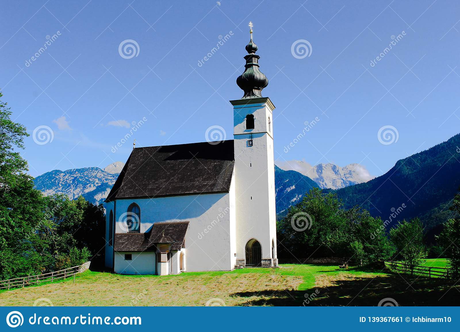 A church on a hill in front of the Alps