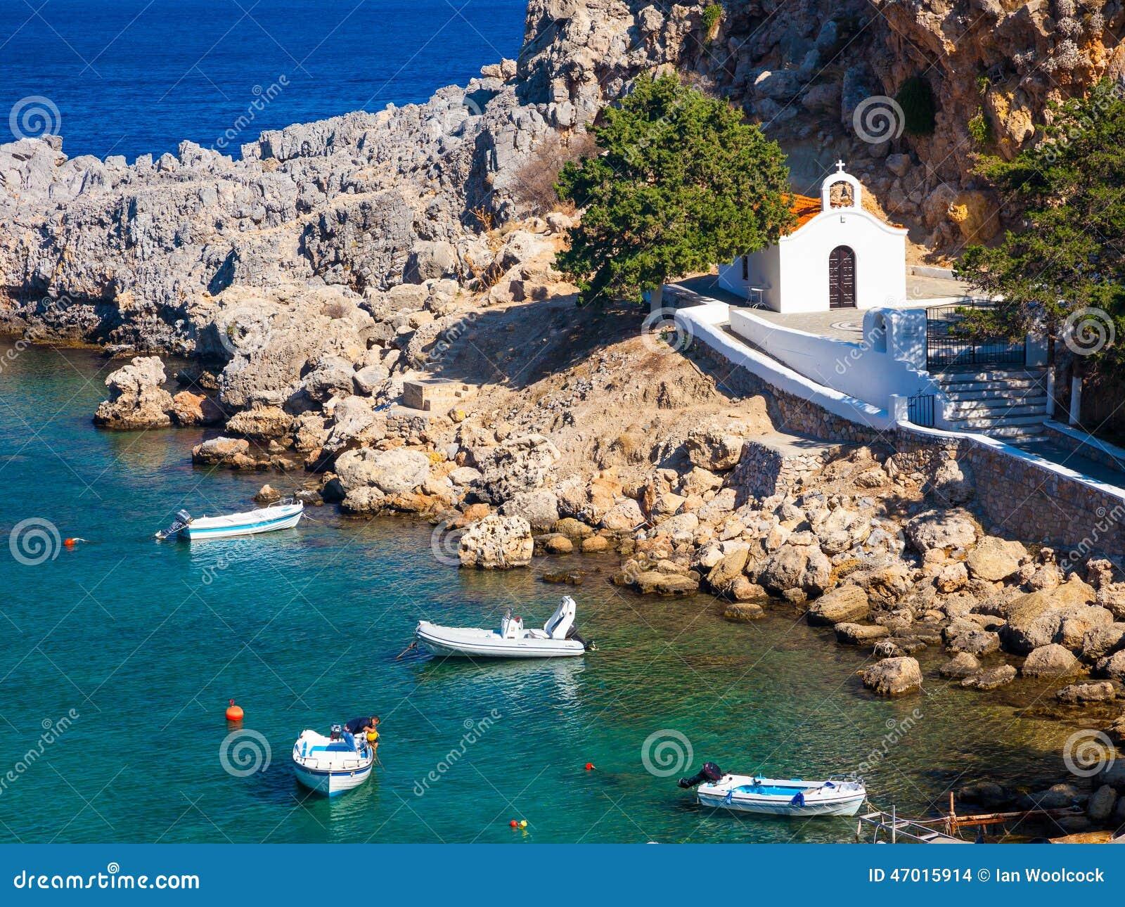 Tiny church and boats at St Pauls Bay Lindos Rhodes Greece Europe.