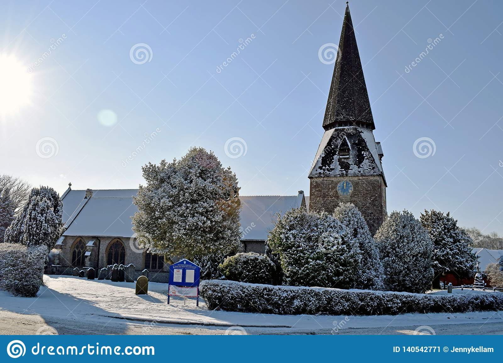 A snowy winter scene of a Church and church yard all cover in white snow