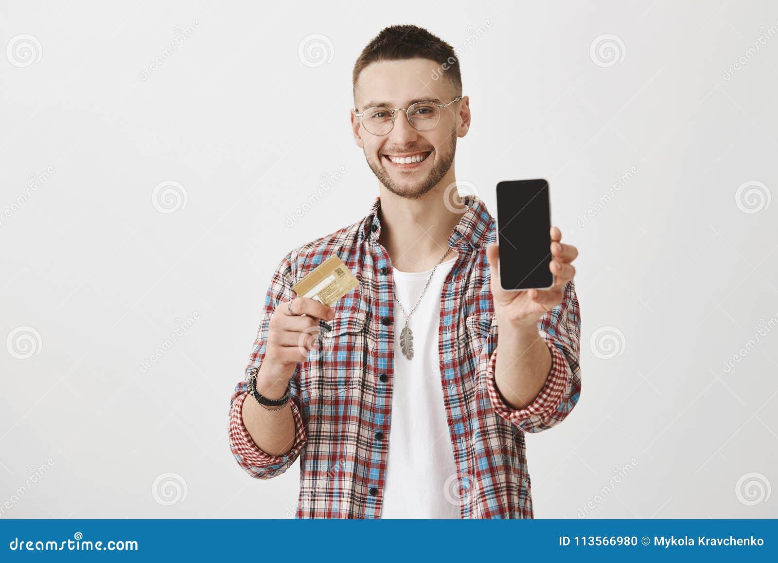 Chwyta twój kredytową kartę i kupuje ten telefon Portret atrakcyjny zadowolony młody człowiek z szczecina i eyewear, ciągnie