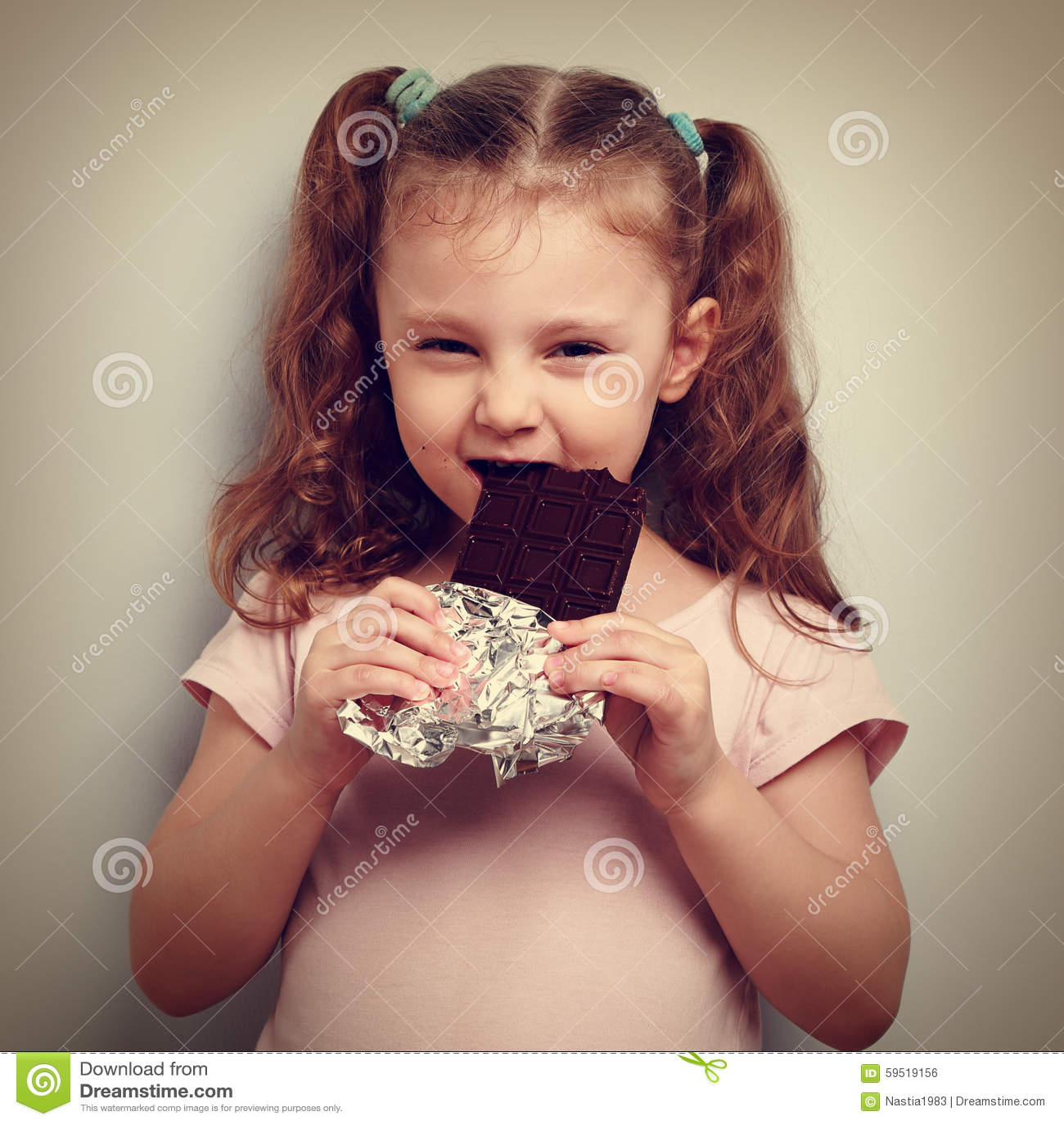 Chytrego dzieciak dziewczyny łasowania ciemna czekolada z przyjemnością, ciekawy i