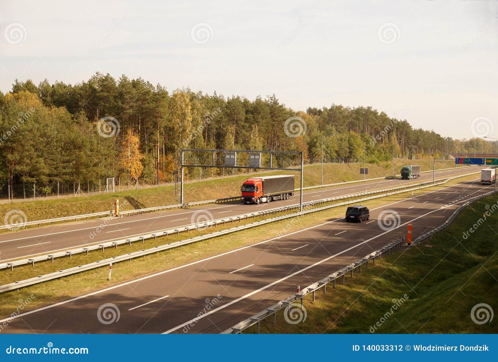Ciężarówki i samochody podczas gdy jadący, w tle elektroniczna opłaty drogowej kolekcja i autostrada