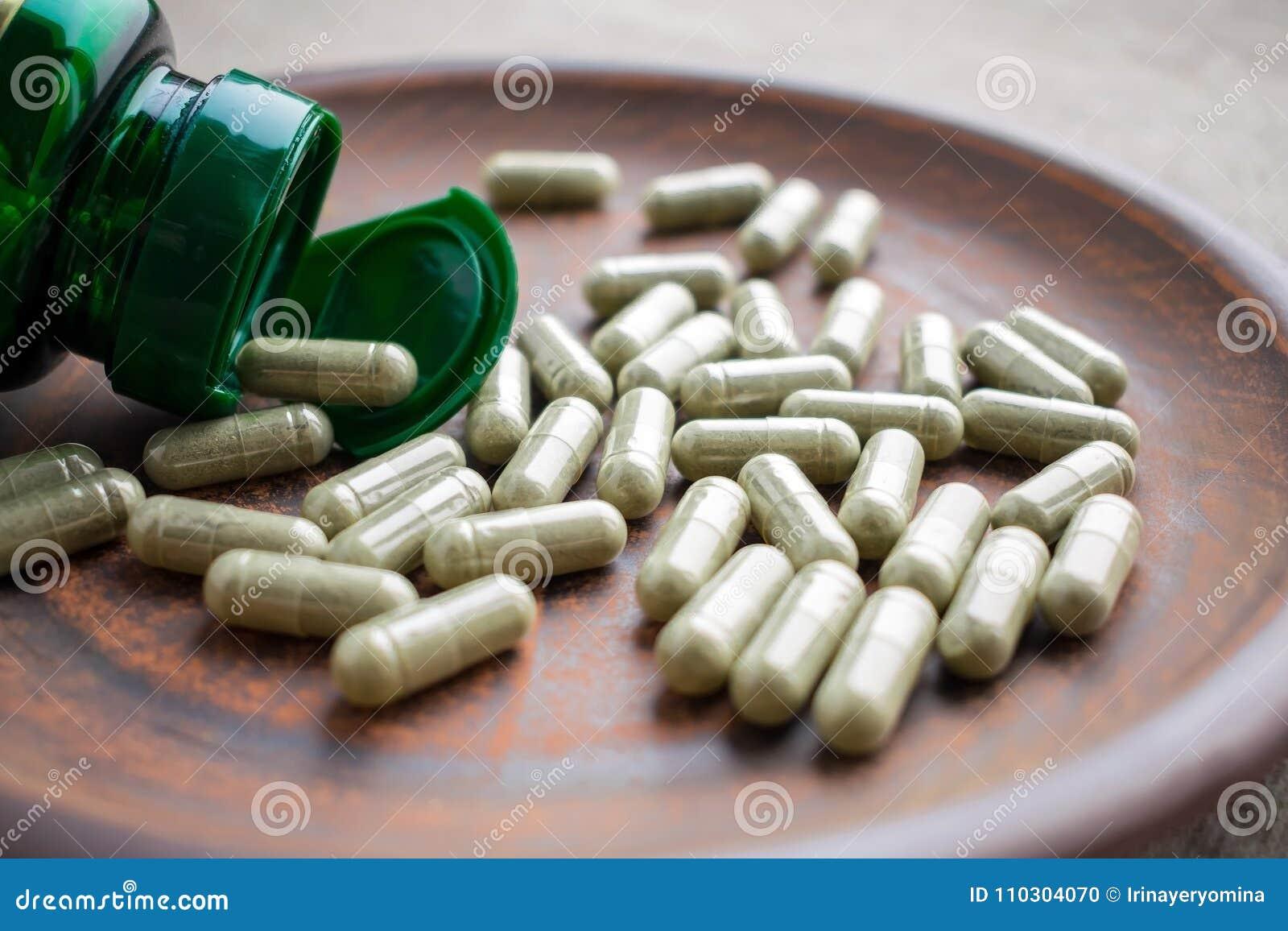 Ciérrese encima de cápsulas del extracto del té verde y embotelle en un marrón p de la arcilla