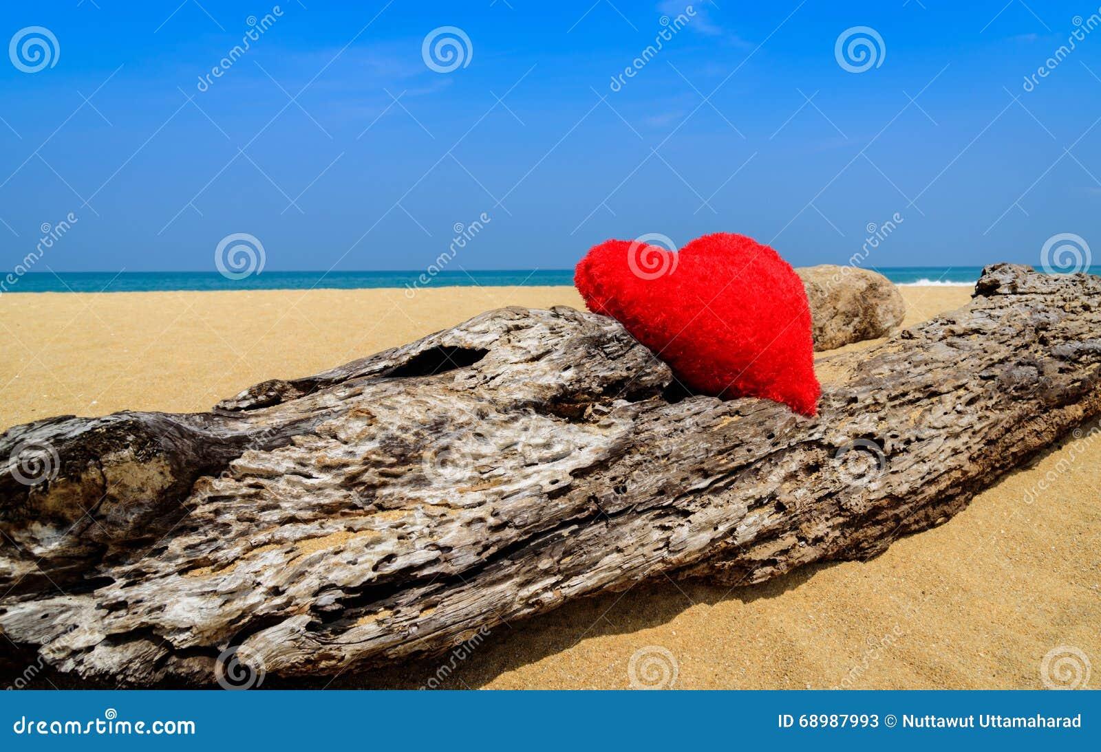 Ciérrese encima de corazones rojos en la arena de la playa del océano - ame el concepto para el holid