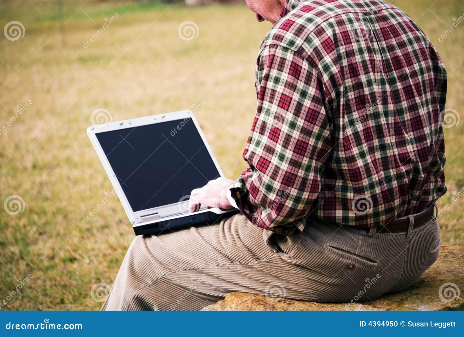 Ciérrese encima de hombre con la computadora portátil