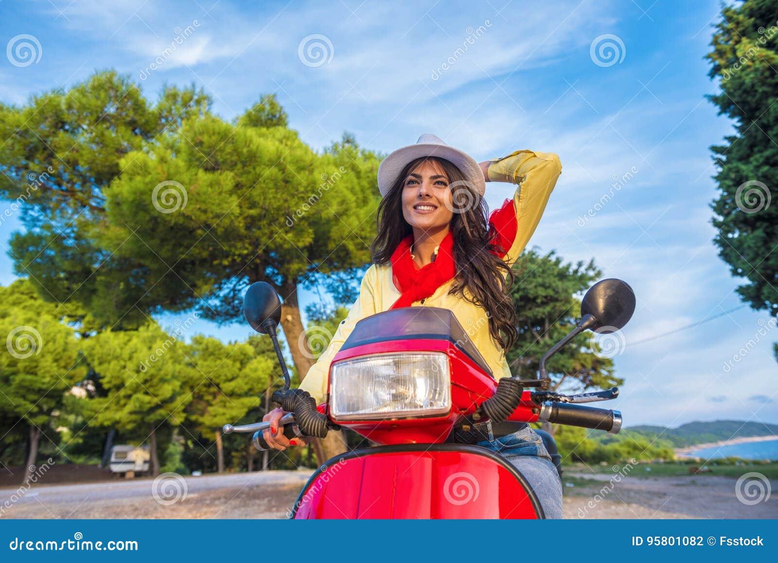 Ciérrese encima de imagen de la forma de vida de la mujer de moda joven en el equipo casual que se sienta en la vespa en la calle