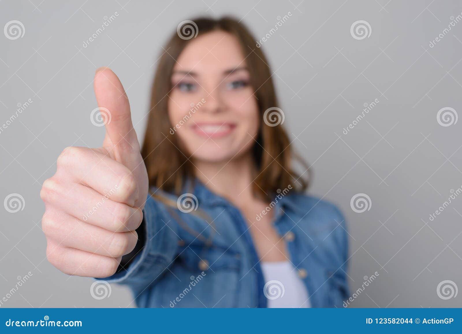 Ciérrese encima de la foto de la mujer linda feliz sonriente en la ropa casual que muestra el pulgar para arriba La aíslan en bue