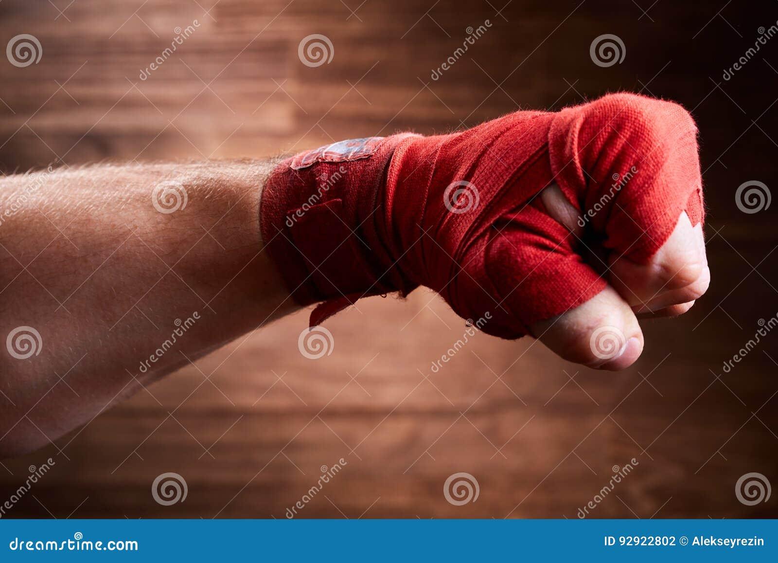 Ciérrese encima de la imagen del puño de un boxeador con el vendaje rojo contra fondo marrón