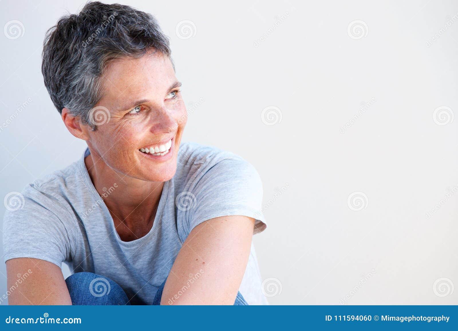 Ciérrese encima de la más vieja mujer hermosa que sonríe contra el fondo blanco