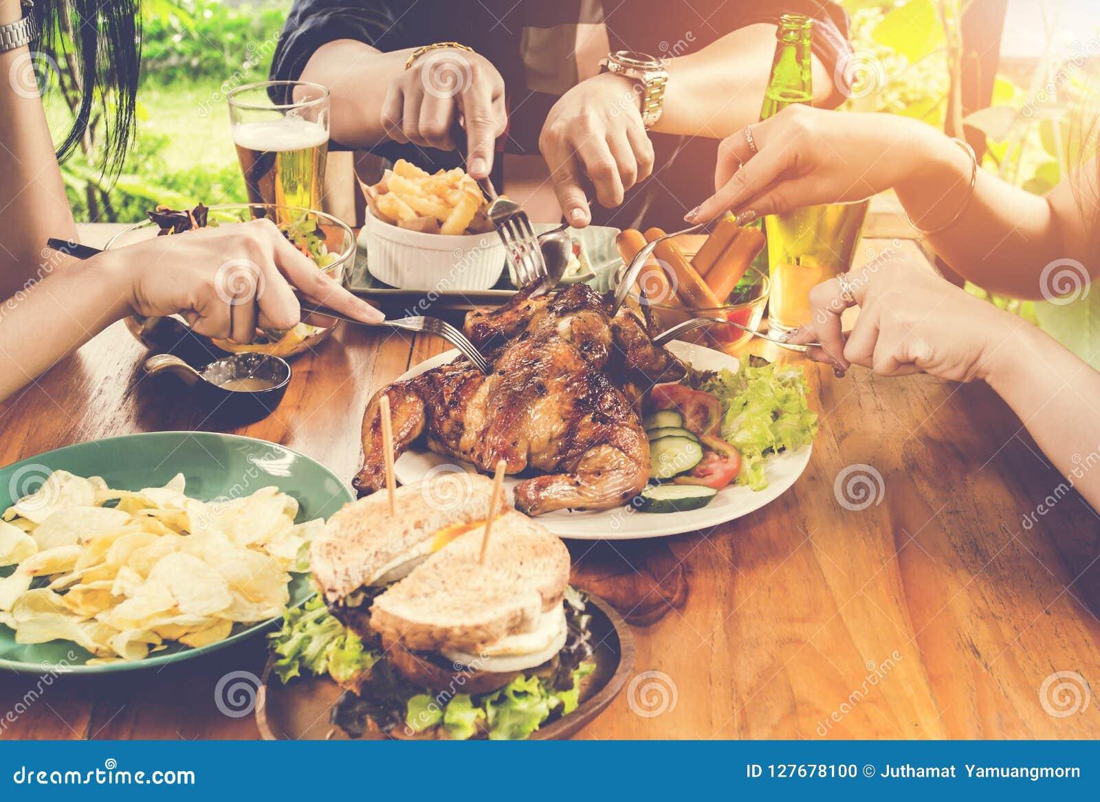 Ciérrese encima de la mano, comiendo Grupo de personas que cena concepto, con la asación del pollo, ensalada, patatas fritas en l
