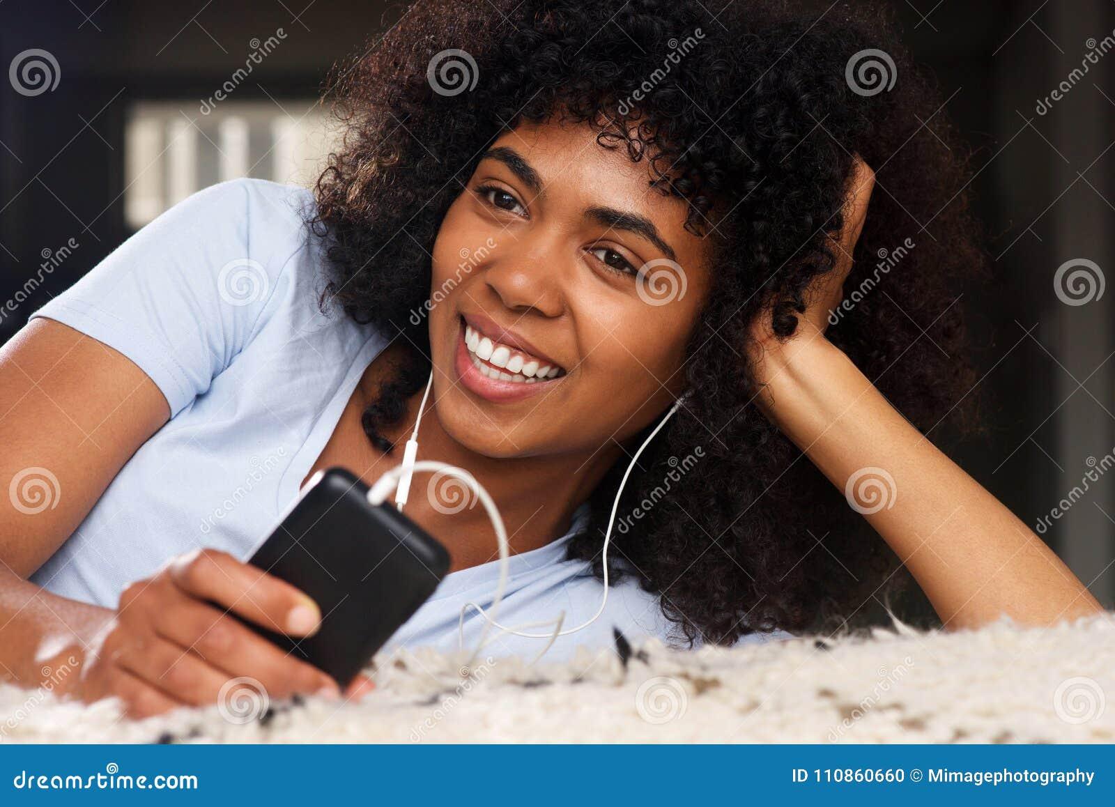 Ciérrese encima de la mujer africana joven hermosa que miente en el piso que escucha la música con los auriculares y el teléfono