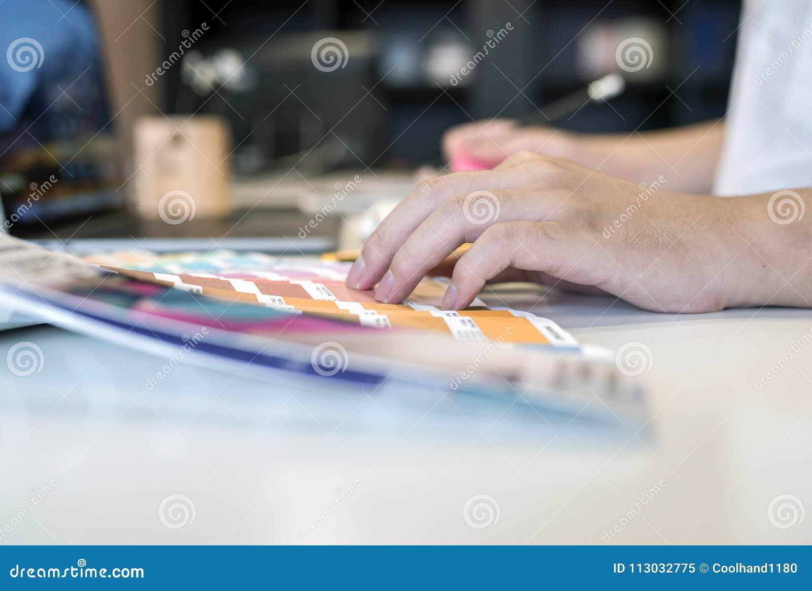 Ciérrese encima de la opinión el diseñador de sexo masculino que señala en muestra de la sombra del color