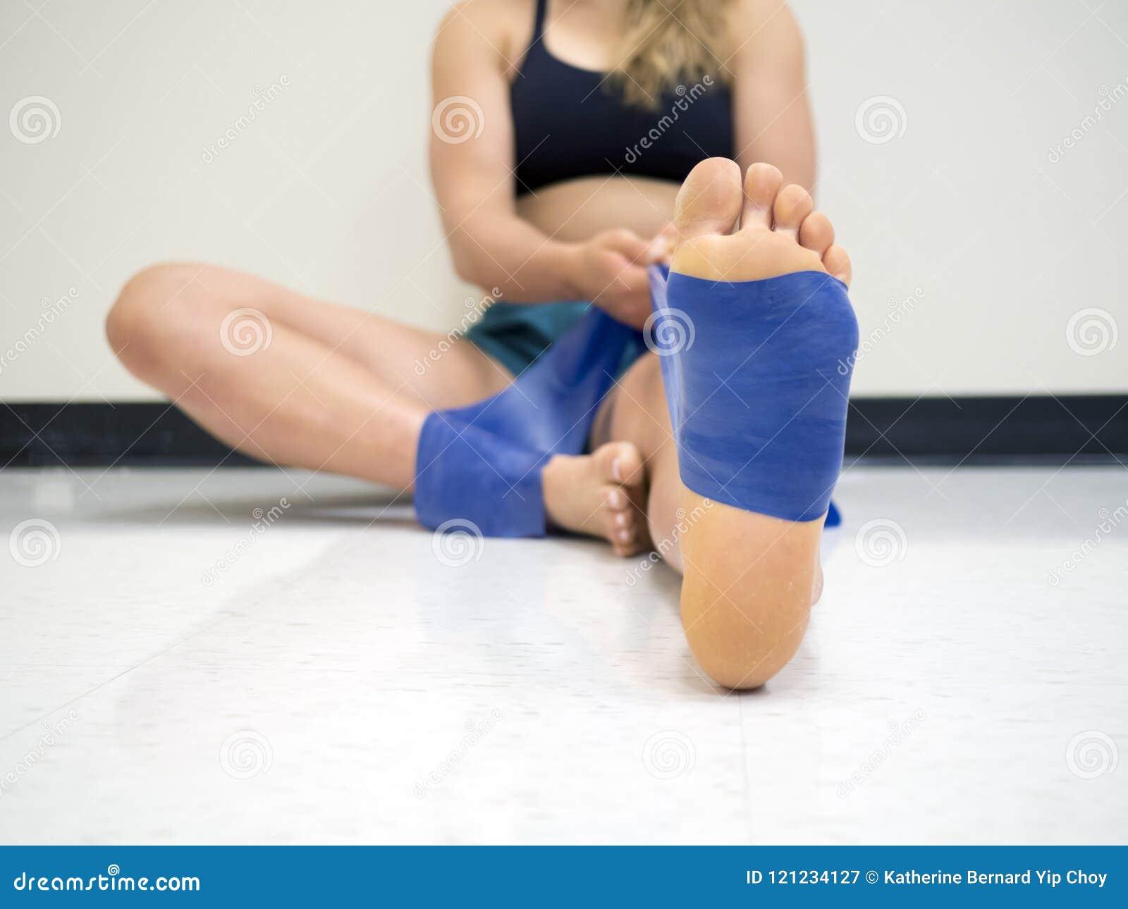Ciérrese encima de la opinión inferior un atleta de sexo femenino joven que usa una banda de la resistencia del theraband en su p