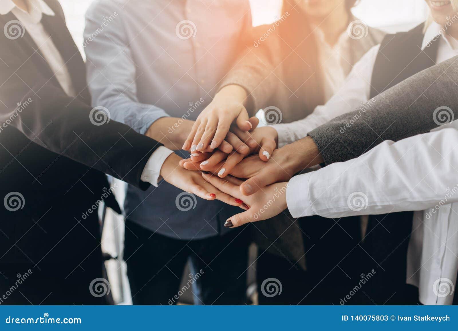 Ciérrese encima de la opinión superior los hombres de negocios jovenes que ponen sus manos juntas Pila de manos Unidad y concepto