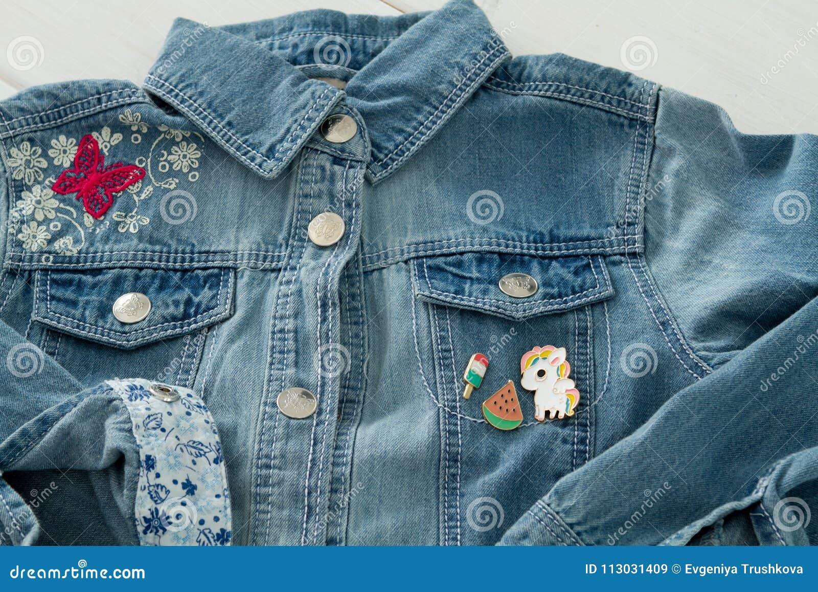 Ciérrese encima de la vista de la chaqueta de los vaqueros del dril de algodón con los pernos gráficos frescos