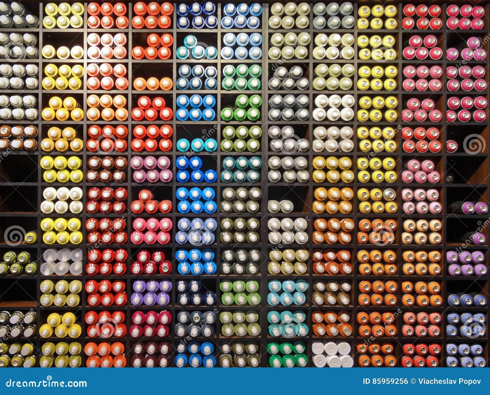 Ciérrese encima de la vista del estante con el espray multicolor usado de la pintada