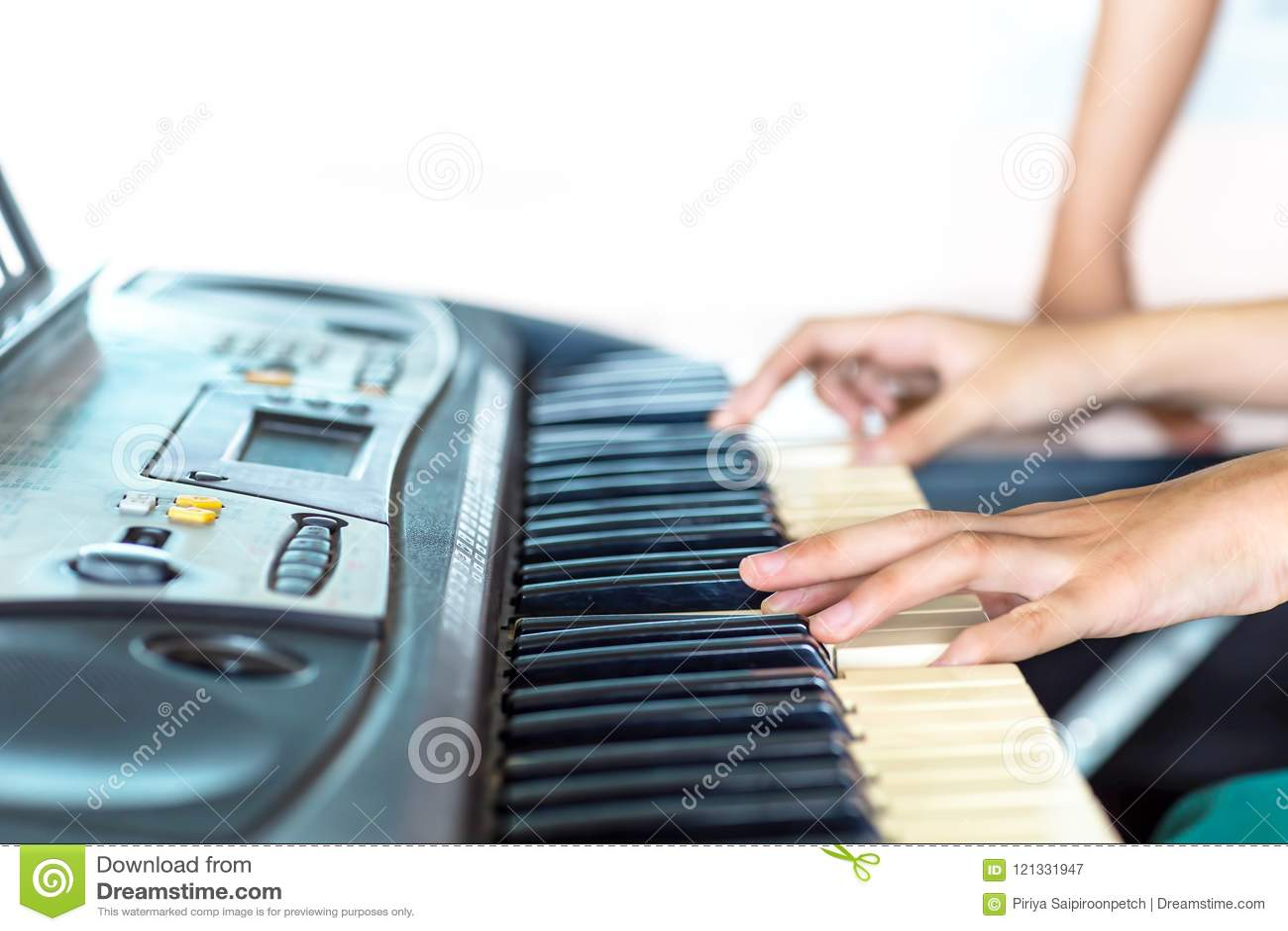 Ciérrese encima de la vista lateral de las manos de la mujer que juegan el piano con la mano del fondo borroso del instructor